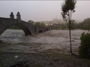 Immagine del ponte gobbo con il fiume Trebbia in piena